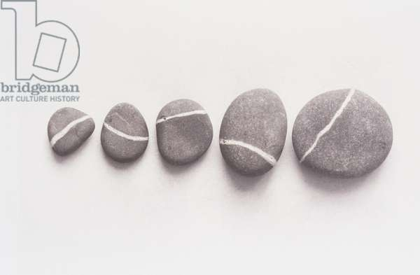 Composition of five pebbles with white lines