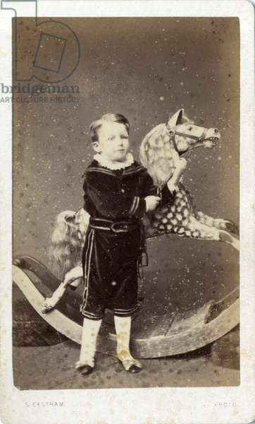 Young boy standing by a rocking horse, 1870s (albumen print)