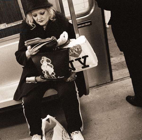 Woman reading on a subway with a Marilyn Monroe purse and an 'I Love New York' bag, 2004 (b/w photo)
