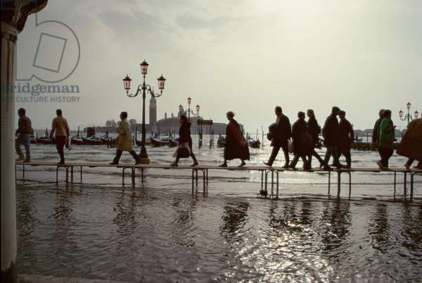 People walking across the Piazzetta on duckboards during High Water (photo)