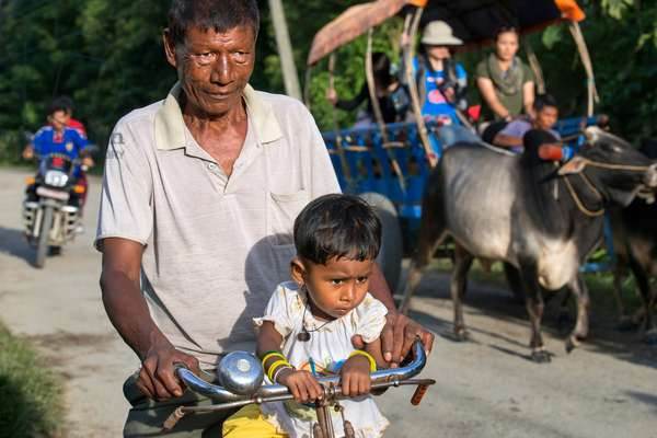 Father with her doughter in a bicycle in Chitwan National Park, Nepal (photo)