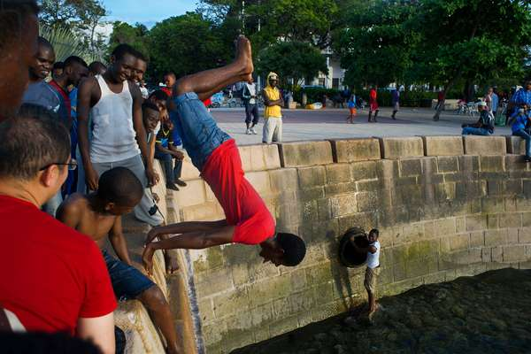 Local boys jumping off the Malecon into the sea next to the pier in Stone Town, Zanzibar, Tanzania, Africa (photo)