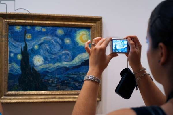 A visitor photographs 'Starry Night' by Vincent Van Gogh at the Museum of Modern Art, New York (photo)