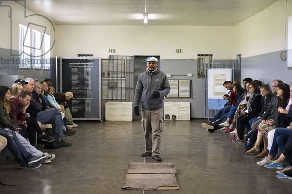 Tourists and prisioner in prisoners cell on Robben Island, Robben Island, prison grounds for political prisoners during apartheid in South Africa., 2018 (photo)