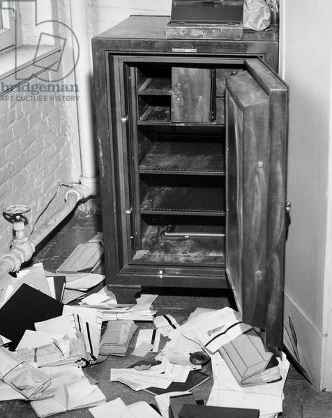 Documents scattered in front of an open safe