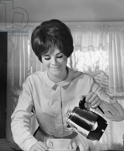 Close-up of a young woman pouring coffee into a cup from a coffee pot