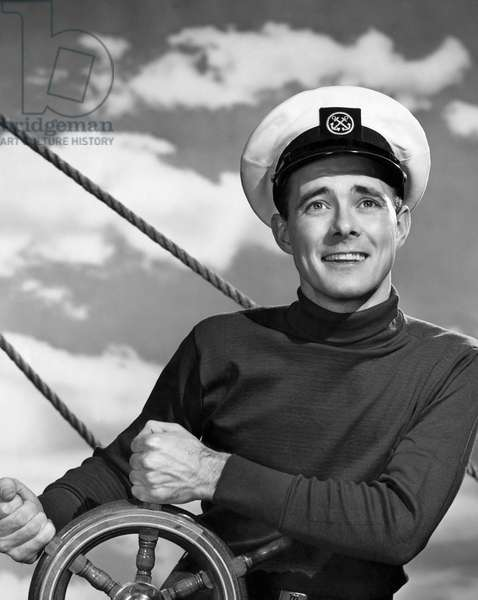 Sailor steering boat and smiling