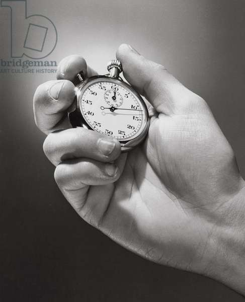 Close-up of a person's hand holding a stopwatch
