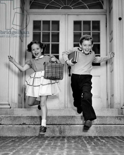 Schoolboy and schoolgirl jumping from steps