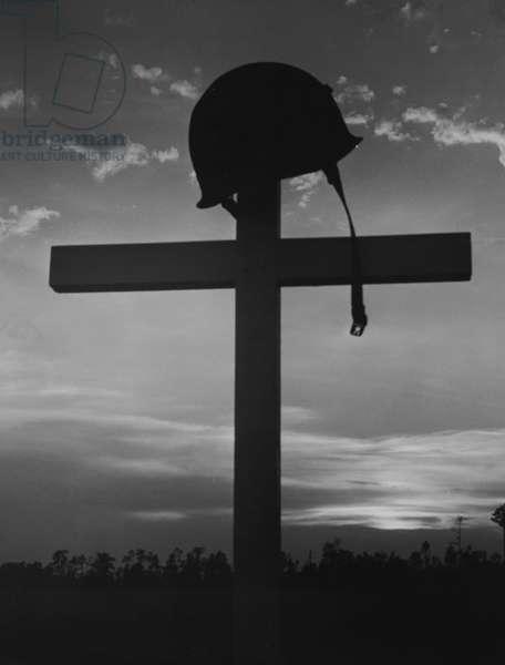 Silhouette of a helmet on a cross
