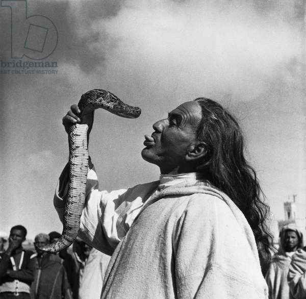 Snake charmer sticking his tongue out and holding a snake, Marrakesh, Morocco