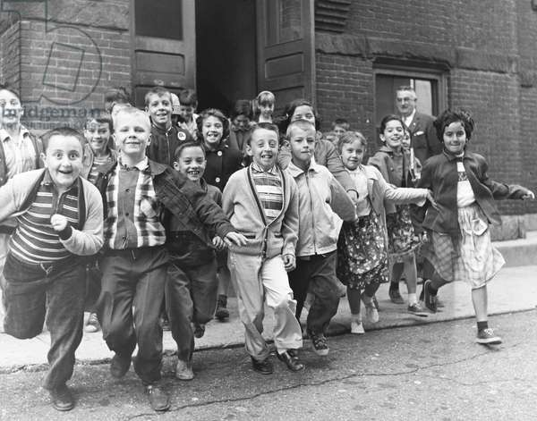 Schoolboys and schoolgirls running out from a school
