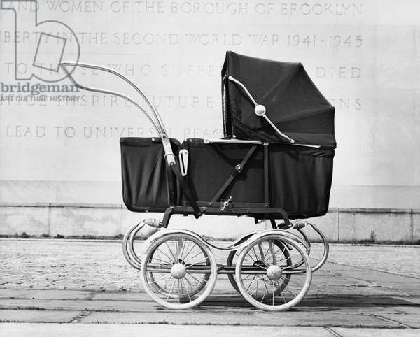 Baby carriage in front of a wall