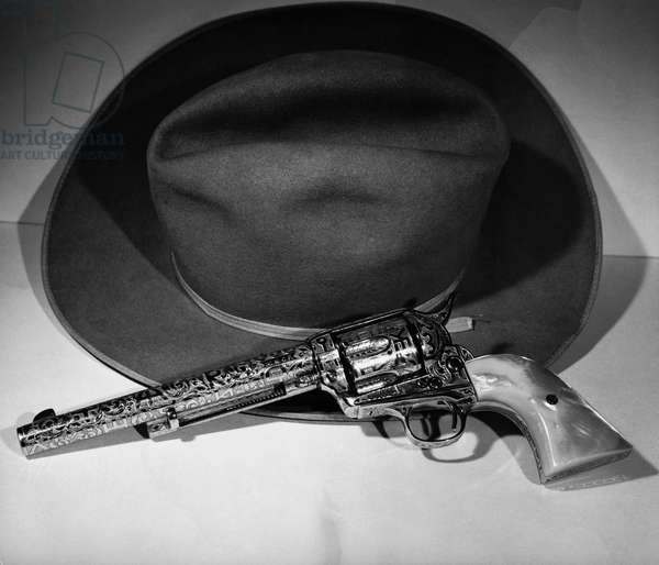 Close-up of a revolver and a hat
