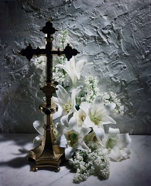 Easter Lily flowers near a crucifix