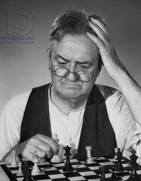Close-up of a mature man playing chess