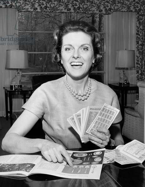 Young woman holding coupons and smiling