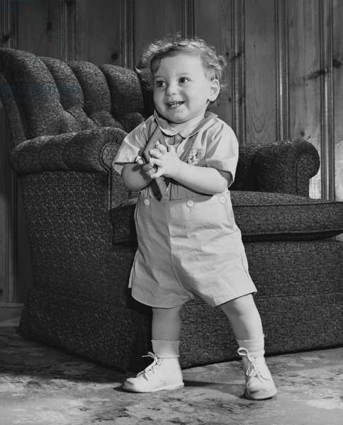 Baby boy standing and holding a picture frame
