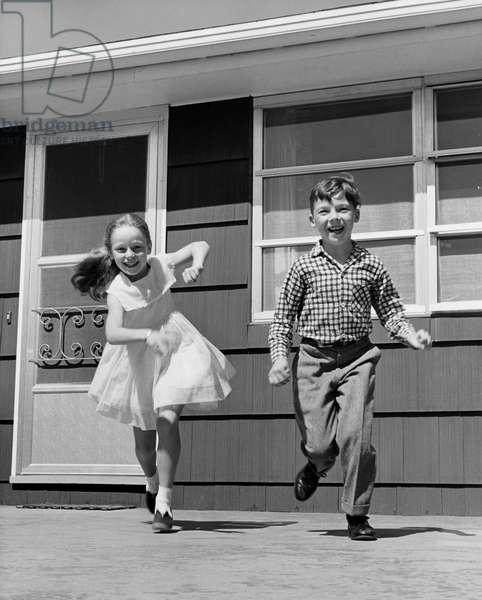 Girl running with her brother and smiling