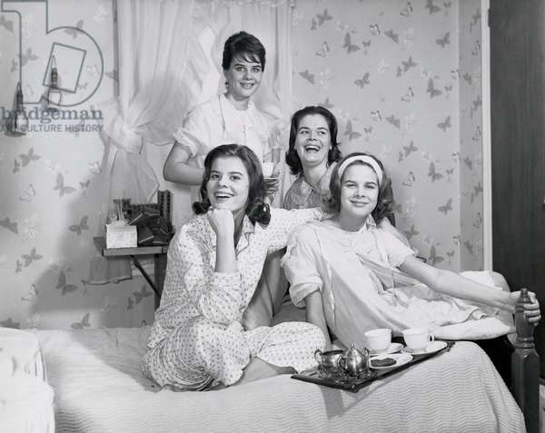 Four teenage girls sitting on the bed and smiling