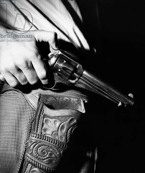 Mid section view of a man holding a revolver