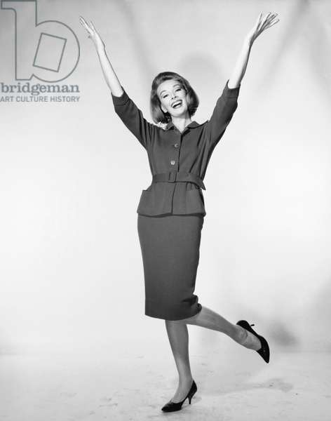 Mid adult woman standing with her arms raised and smiling