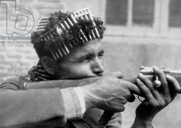 Moroccan soldier with cartridges curled around his head targeting with his rifle, Spanish Civil War