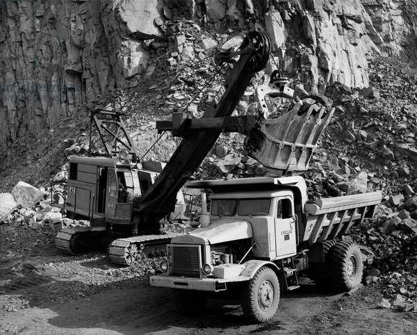 Earth mover loading rocks in to a dump truck