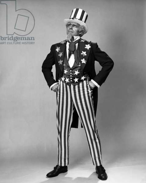 Senior man in Uncle Sam costume standing with arms akimbo