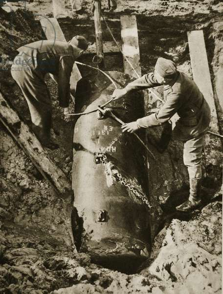 A 3600 pound unexploded bomb is lifted with steel cables from a dummy anti-aircraft post near the Siemens cable factory in Berlin-Gartenfeld, 1940-45 (b/w photo)