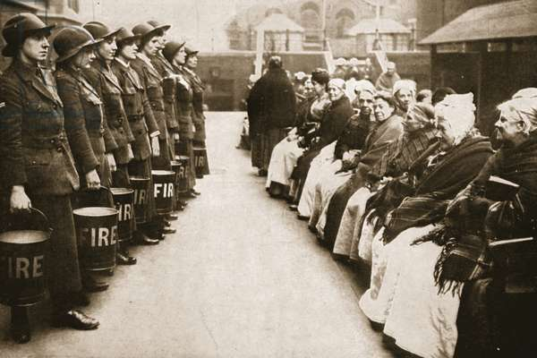 Women fire workers doing a demonstration for the elderly women at a home in East London, from 'The Illustrated War News' (b/w photo)