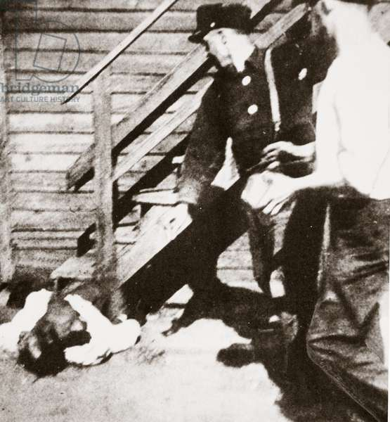 Two white men stoning an African American to death, 1919 (b/w photo)