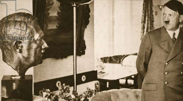 Adolf Hitler regards a bust of himself (b/w photo)