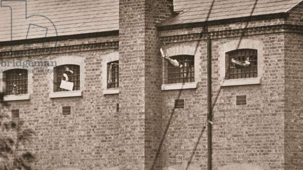 The hunger strikers waving to Christabel Pankhurst from their cells in Holloway Prison, 1909 (sepia photo)