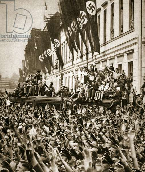 At the corner of Vosstrasse and Wilhelmplatz, in front of the new Reich Chancellery, the radio car offers a good view over the heads of the crowd, 19th July 1940 (b/w photo)