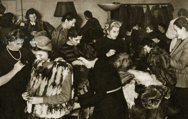 At a winter clothing collection point, fur coats are altered for use on the Eastern Front, 1941 (b/w photo)