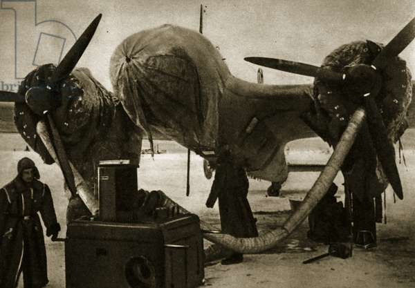 In the bitter cold of the far north near the Arctic circle, an aircraft engine is preheated with hot air, 1941-5 (b/w photo)