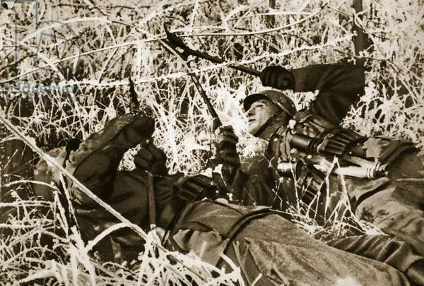 German soldiers clear a way through the barbed wire in no man's land, 1939 (b/w photo)