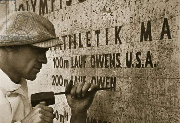 Carving the name of Jesse Owens into the champions' plinth at the 1936 Summer Olympics held in Berlin (b/w photo)