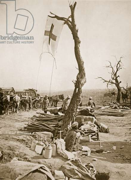 An advanced dressing-station: A Red Cross flag is affixed to a tree, 1916 (sepia photo)