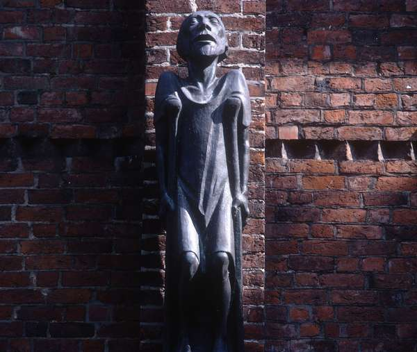 Sculpture of a blind beggar with crutches on the wall of the cathedral, 1930 (bronze)