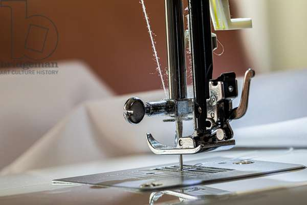 Sewing machine up close, on the foot and the needle, making smocks for caregivers, April 2020 (photo)