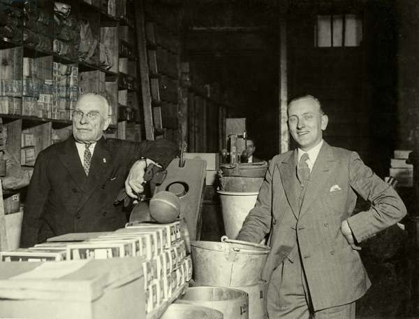 Millionaire returns to his East End home, Sir Joynton Smith in his father's old shop with his nephew, Mr A. J. Smith (b/w photo)