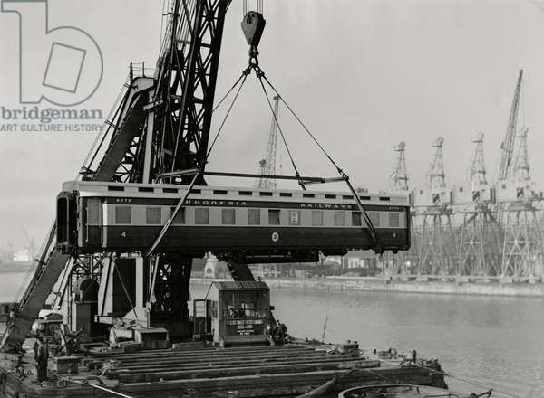 Rail coaches for export to Rhodesia being loaded by PLA 'Ajax' in South West India Dock, London (b/w photo)