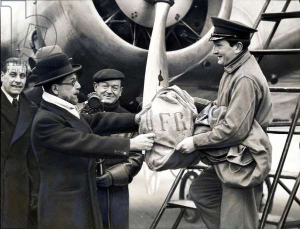 Monsieur Gentin giving the first sack of post to the Air France pilot at the inauguration of the first postal airline without surtax from Paris to Nice, Le Bourget, 16 February 1938 (b/w photo)