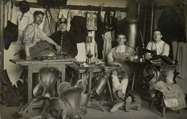 Group portrait of a soldier and men repairing boots and clothing (b/w photo)