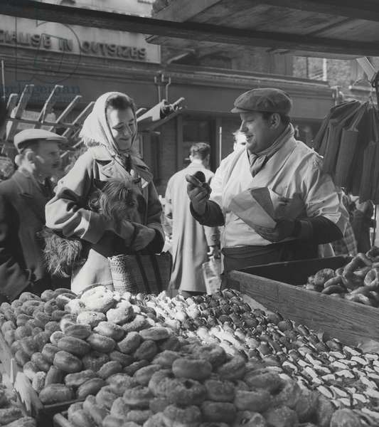 Woman with a small terrier buying bagels at a market stall, possibly London, c.1945-50 (b/w photo)
