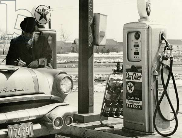 A man refills his Pontiac Star Chief, c.1959 (b/w photo)