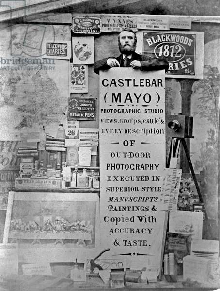 Photographer Thomas Wynne poses for a colleague inside his studio at his shop in the Main Street of Castlebar, Ireland, October 1871 (albumen print)