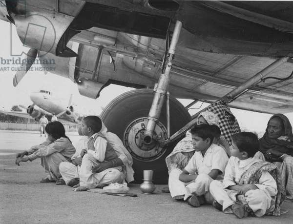 Evacuation by air: refugees awaiting their turn at Peshawar Airport for the flight to India during the Partition Migration, 1947 (b/w photo)